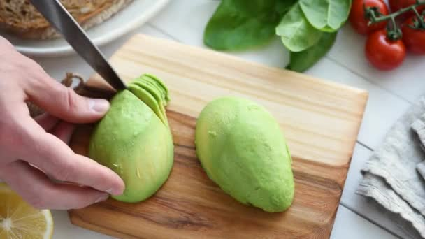 Male hands cutting avocado on wooden board. Cooking process.