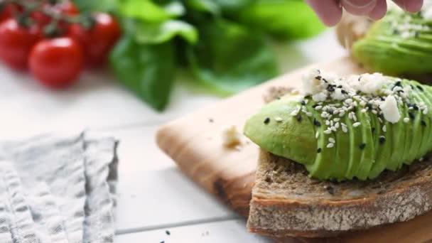 gesunde Avocado-Toast zum Frühstück. Toast mit Sesam garnieren. Konzept der gesunden Ernährung und Lebensweise