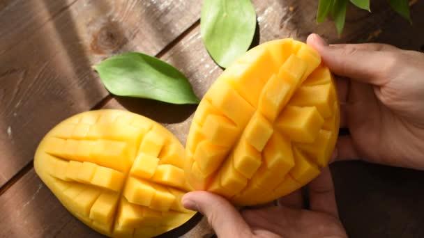 Osoba otevírá řez mango přes dřevěné pozadí stolu. Zdravé jídlo, šťavnaté tropické ovoce