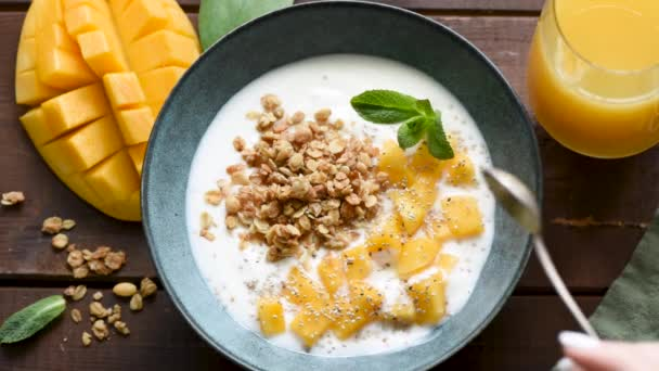 Slow motion eating yogurt with mango and granola. Top view, wooden table background. Concept of healthy eating, healthy lifestyle