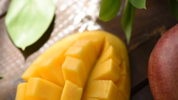 Tasty mango on a wooden table, closeup view. Healthy vegan or vegetarian yellow food rich in vitamins