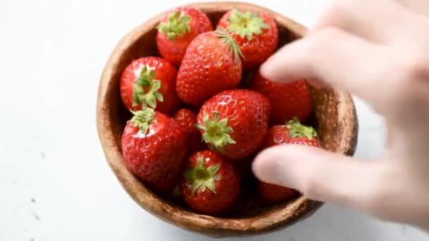 Sbíjím jahody ze záběru času na misce. Koncepce zdravého stravování, veganu, vegetariánská strava