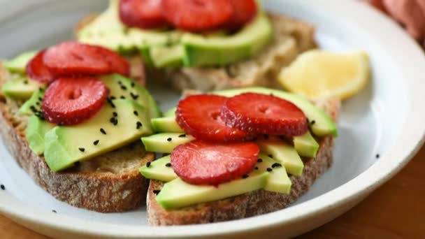 Healthy food. Bread toast with avocado and strawberry on plate, closeup view