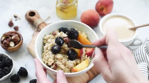 Člověk konzumní ovesnou kaši s ovocem a medem. Zdravá snídaně, zdravá jídla a životní styl, dietu a úbytek váhy