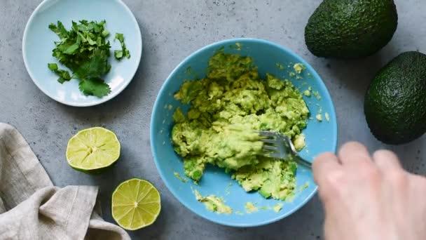 Hände zerdrücken Avocado in einer Schüssel mit einer Gabel. Bilder von der Tischplatte. Gesunde Ernährung