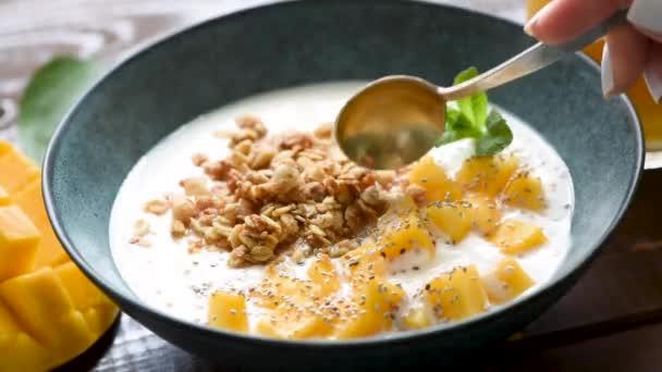 Müsli mit griechischem Joghurt und Mango in Schüssel. einen Löffel Joghurt zu sich nehmen. gesunde Ernährung, gesunder Lebensstil. Nahaufnahme