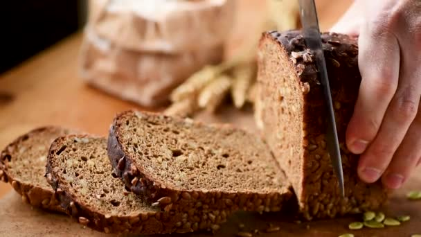 Person slicing fresh rye bread with seeds on cutting board. Closeup view