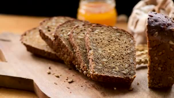 Rotating sliced loaf of rye bread with sunflower seeds on wooden cutting board