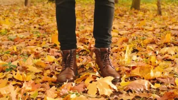 Muž v kožených botách v podzimním parku, stojící na javorových listech. Sezónní podzim pozadí záběry plné Hd