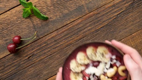 Mužské ruce servírují superfood acai smoothie misku s polevou v kokosové misce. Horní pohled. Veganský paleo dietní koncept