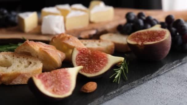 Sýrový talíř s camembert nebo brie sýrem, fíky, bagetou a hrozny. Ženská ruka sbírá plátek camembertského sýra. Sada předkrmů
