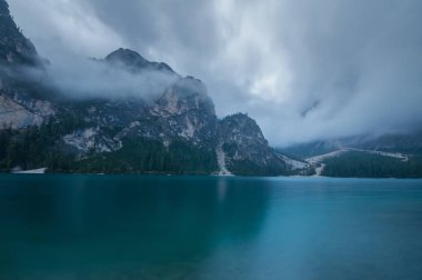 Cloudy and foggy morning on the alpine lake Lago di Braies, dolomites, italy stock vector
