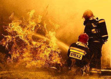 İtfaiyeciler tehlikeli bir yangını söndürüyorlar.