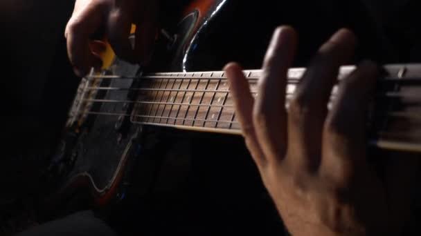 Hudebník hraje na baskytaru. Tmavé pozadí. Closeup