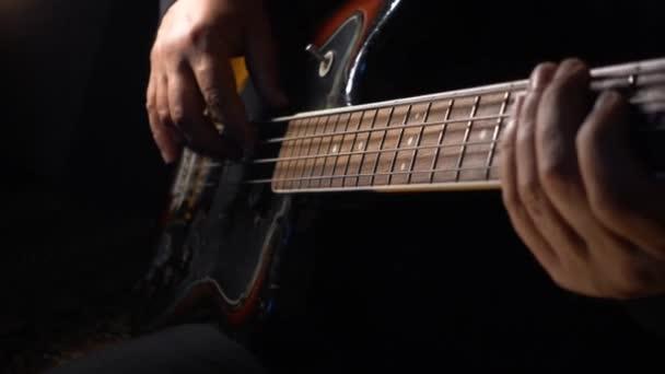 Musician Plays Bass Guitar . Dark background . Closeup