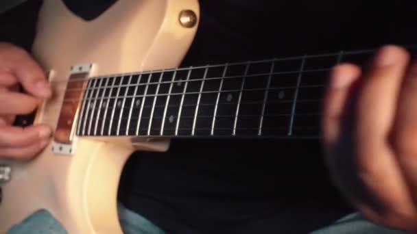 hudebník hraje na bílou kytaru ve studiu