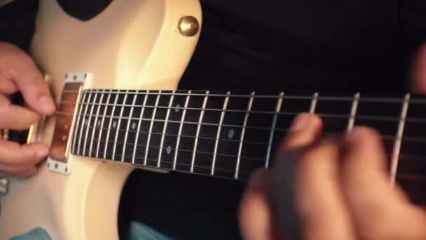 musician playing white guitar at studio