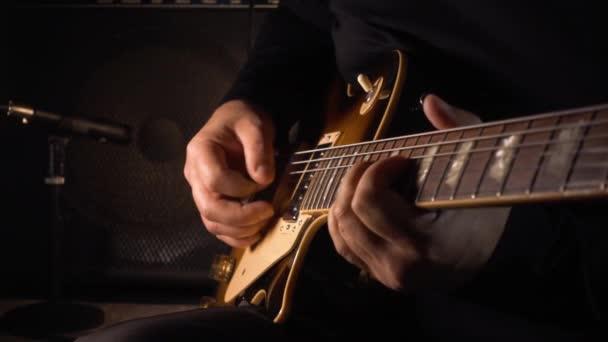 hudebník hrající na kytaru ve studiu