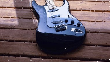 electric guitar on the wooden board behind the glass with water drops