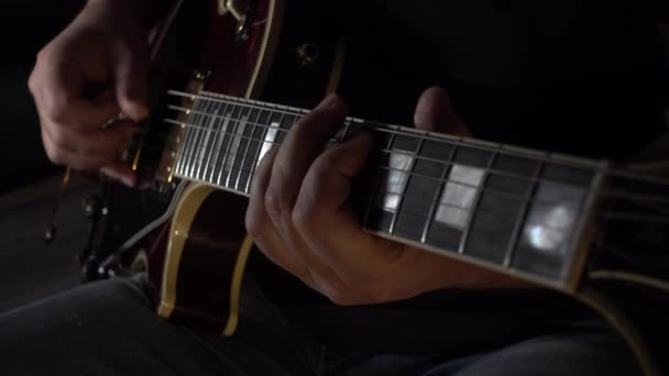 Hudebník hraje ve studiu na kytaru. detailní záběr. Tmavé pozadí