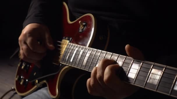 Musician plays guitar at studio . closeup . Dark background