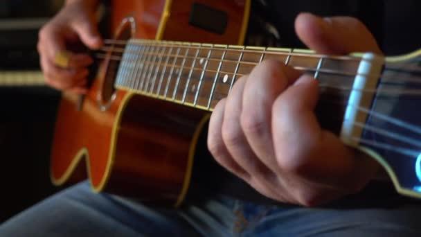 hudebník hraje na kytaru ve studiu