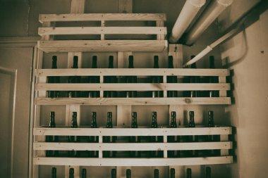 Old bottles of dark glass on a shelf of wooden planks