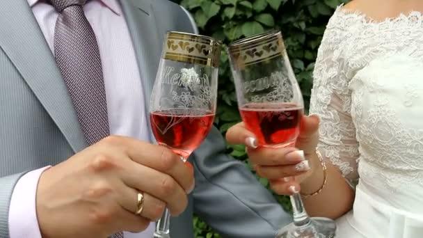 A menyasszony és a vőlegény pezsgővel. Friss házasok koccintanak egy esküvőn. A menyasszony és a vőlegény borospoharakkal a kezükben..