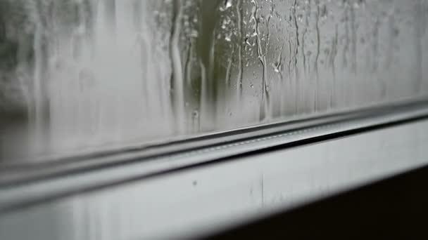Déšť prší na okno. Dešťové kapky klepající na skleněná okna. Šedý deštivý depresivní výhled zevnitř domu.
