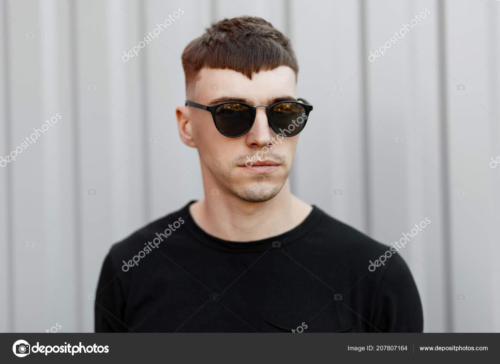 ac7561b6749 La mode portrait d un jeune homme élégant avec lunettes de soleil mode dans  un débardeur noir près du mur gris — Image de ...