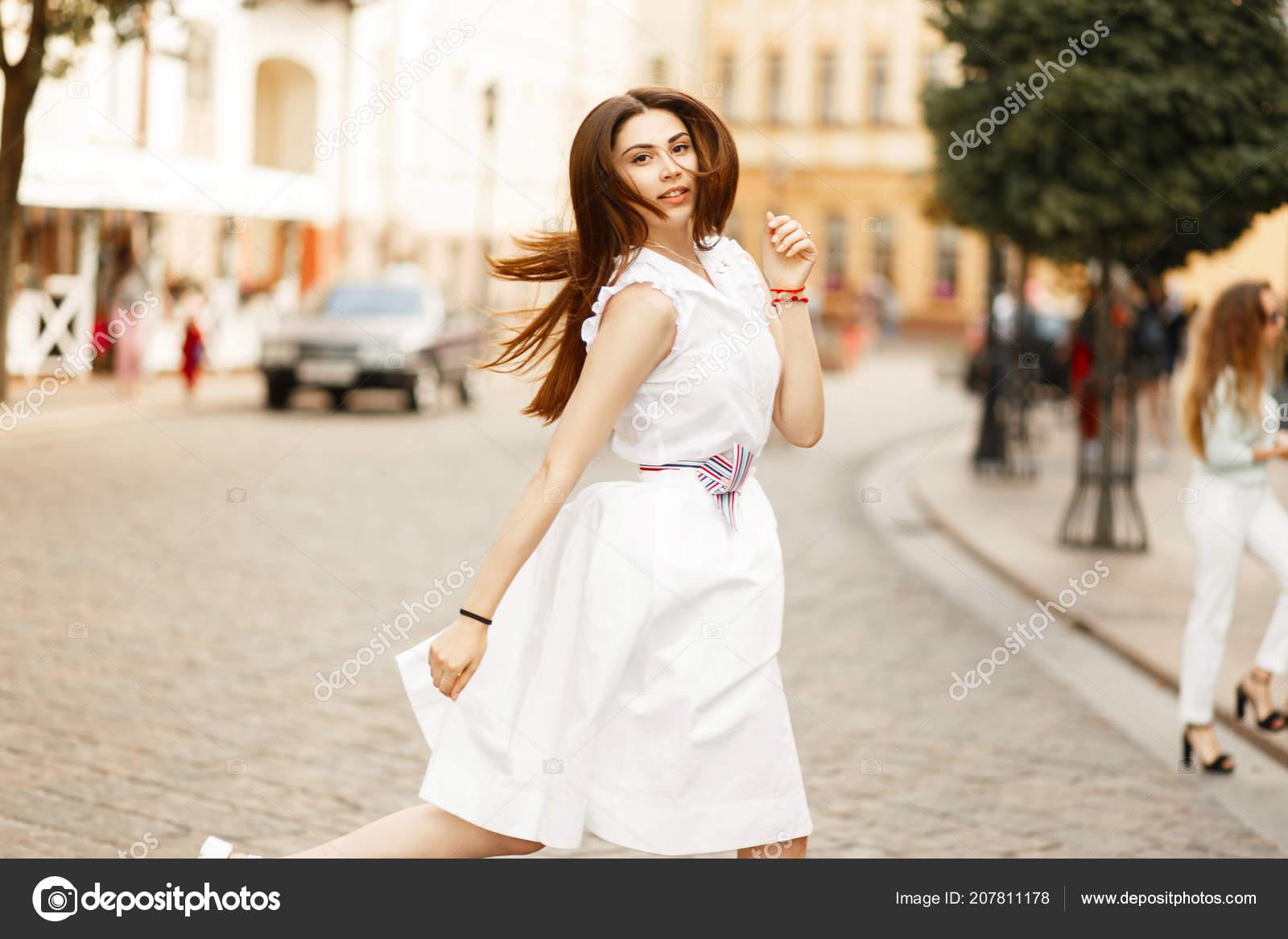 d82a0b6aa652 Giovane donna alla moda in un vestito bianco elegante bella cammina nella  città– immagine stock