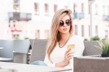 Elegant young hipster woman with blond hair in a knitted white sweater in stylish sunglasses is sitting in a cafe and eating sweet ice cream on a summer day. Beautiful girl on vacation.