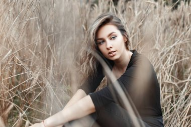 Attractive cute rural young woman in stylish black t-shirt in vintage jeans is resting in a field with dry grass. Pretty beautiful girl model enjoys nature in the village on an autumn warm day.