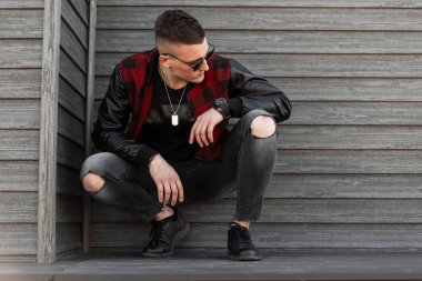 Pretty handsome young hipster man in black sunglasses in trendy red checkered jacket in sneakers in stylish ripped jeans is sitting outdoors near a wooden wall. American guy is resting.