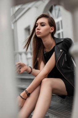"""Картина, постер, плакат, фотообои """"Европейская молодая модель в элегантном коротком черном платье в стильной черной кожаной куртке сидит на каменной лестнице рядом с современным белым зданием. Девочка отдыхает в городе в осенний день."""", артикул 312737500"""
