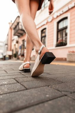 Fashion woman with pretty legs in stylish summer sandals walks on a stone road in the city. Back view. Close-up