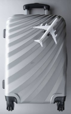 Flat lay grey suitcase with mini airplane on grey background. tr