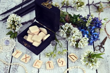 Magic runes in black box with spring wildflowers and decorations on table. Occult, esoteric and divination still life. Halloween background with vintage objects