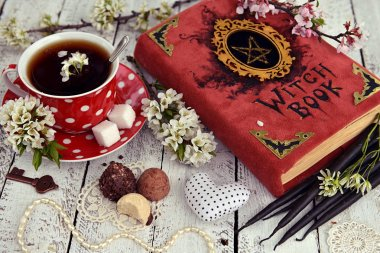 Red cup of flower tea with black candles, candies and witch book on table. Occult, esoteric and divination still life. Halloween background with vintage objects stock vector