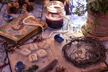 Old tarot cards deck, runes and dried roots with book on table. Magic gothic ritual. Wicca, esoteric and occult background with vintage objects