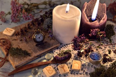 Wooden runes, healing herbs, black and white candles and diary book on lace napkin. Magic ritual. Wicca, esoteric and occult background with vintage witch objects