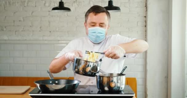 Šéfkuchař pracuje s lékařskou maskou obličeje v kuchyni kavárny, restaurace.