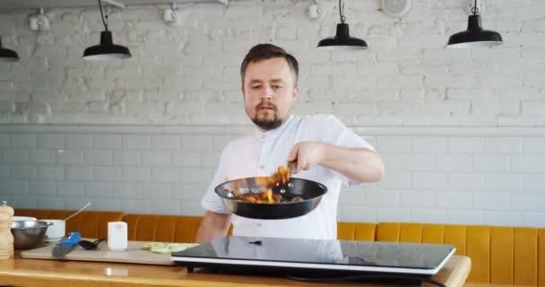Kuchařské házení zvrací pálení s ohnivou zeleninou na pánvi. Míchání kusů