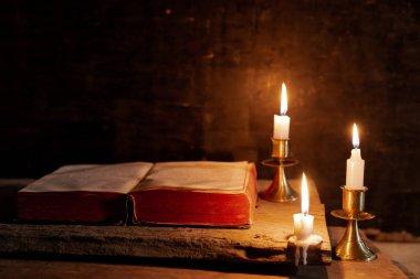 İncil bir mum yanındaki bir masada açık.