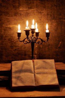 Eski bir meşe ahşap masa üzerinde Kutsal Kitap ve mum açık.