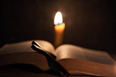 Eski bir meşe ahşap masa üzerinde İncil ve mum ile çapraz.