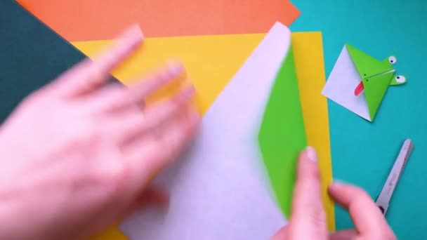 Step 1. female hands make paper bookmark. Step-by-step instructions on how to make origami paper bookmark frog. Simple diy with kids childrens concept.