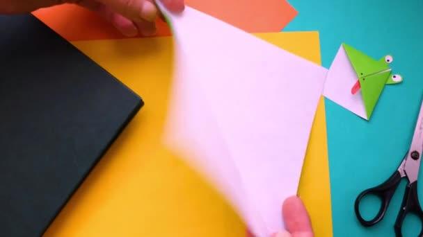 Schritt 2. Frauenhände machen Lesezeichen aus Papier. Schritt-für-Schritt-Anleitung, wie man Origami-Papier Lesezeichen Frosch zu machen. Einfaches Diy mit Kinderkonzept.