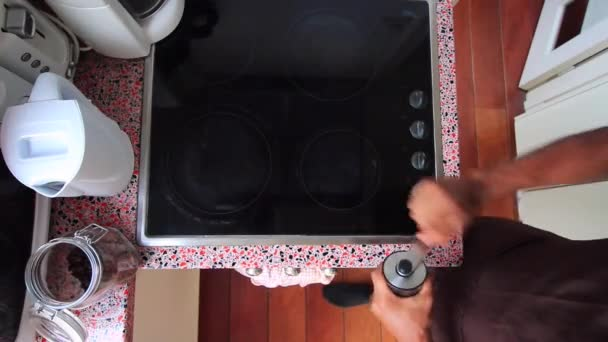 Top view person manually grinding Brazilian roasted coffee beans