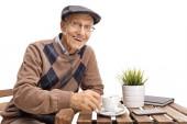 Starší muž, sedící u stolu kávu a usmívá izolovaná na bílém pozadí
